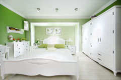 Stylish green bedroom. With big white bed, wardrobe and chest of drawers Royalty Free Stock Image