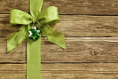 Stylish green ribbon and heart decoration. Tied in an ornamental bow on textured rustic wooden boards for your Xmas greeting or seasonal message royalty free stock photo