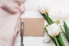 Stylish greeting card template with tulips and crystals and pen. Boho wedding invitation on white wooden rustic background. flat lay. photo workshop. space for Royalty Free Stock Photos