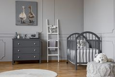 Stylish grey baby room interior with wooden furniture, white scandinavian ladder and teddy bear on pouf, real photo with copy royalty free stock image