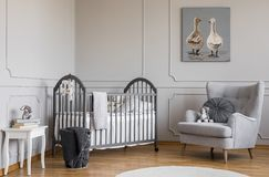 Stylish grey baby room with wooden crib, comfortable armchair and white table with books, real photo with copy space on the empty. Wall, concept stock image