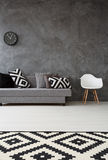 Stylish grey living room idea. Grey living room with sofa, chair, pattern carpet and pillows in black and white Stock Photo