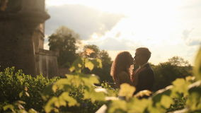 Stylish groom and beautiful bride in white gown have sensual moment at evening park near romantic vintage palace in warm stock video