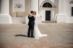 Groom and bride with a bouquet , hug on the street Stock Photography