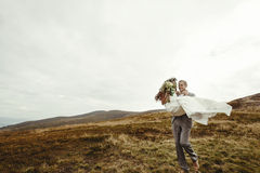 Stylish groom carrying happy bride and having fun, boho wedding. Couple, luxury ceremony at mountains with amazing view, space for text Royalty Free Stock Photography