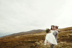 Stylish groom carrying happy bride and having fun, boho wedding. Couple, luxury ceremony at mountains with amazing view, space for text Stock Photos
