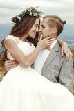 Stylish groom  carrying happy bride and hugging, romantic tender Stock Photography