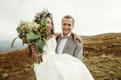 Stylish groom carrying happy bride and laughing, boho wedding co. Uple, luxury ceremony at mountains with amazing view royalty free stock photo