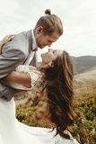 Stylish groom happy holding happy bride in sun light and smiling. Romantic moment, boho wedding couple, luxury ceremony at mountains with amazing view stock images