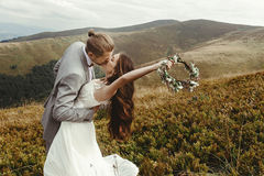 Stylish groom kissing gorgeous bride in sun light, perfect mome. Nt, boho wedding couple, luxury ceremony at mountains with amazing view royalty free stock photo