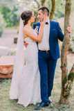 Stylish groom in luxurious blue suit holding his bride white dress with long veil outdoor. A park view is at background Royalty Free Stock Photo