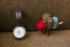 Stylish groom`s accessories on a brown background. Boutonniere and wristwatches. Artwork. Stylish groom`s accessories on a brown background. Boutonniere and Royalty Free Stock Photo