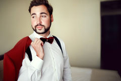 Stylish groom in tuxedo suit marsala red, burgundy bow tie, professional hairstyle, beard, mustache. Wedding Royalty Free Stock Photo