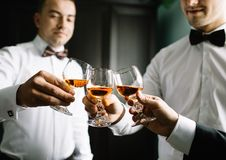 Stylish groomsmen helping happy groom getting ready in the morning stock photography