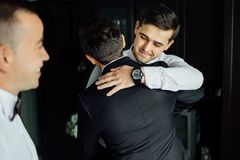Stylish groomsmen helping happy groom getting ready in the morning for wedding ceremony. Stylish groomsmen helping happy groom getting ready in the morning Stock Photo