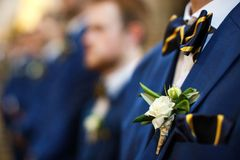 Stylish groomsmen stand during the ceremony in the church.  Stock Photography