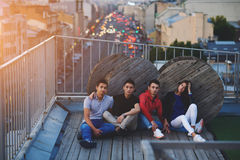 Stylish group of friends posing while sitting on a roof with evening city with lights machines on background, Stock Photo