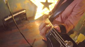 Stylish guitar player rock star plays funky disco music style solo or rhythm on electric guitar. Young man is playing stock footage