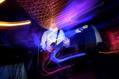 stylish guitarist playing on a stage with a band on wedding reception with cool motion light