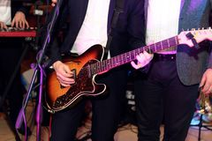 stylish guitarist singer playing on a stage with a band on wedding reception