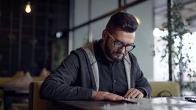 Stylish guy with beard in glasses came in restaurant and choosing food in menu. stock video footage