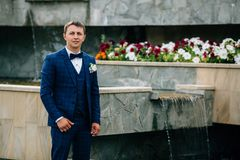 A stylish guy with a bow-tie and a buttonhole poses near an artificial waterfall. A man in a business suit is walking in Stock Images