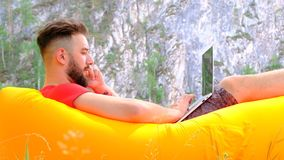 Stylish guy businessman freelancer working on a laptop and talking on a mobile phone. A young man with a beard on the background o stock footage