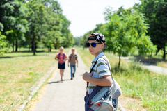 Stylish guy in a cap and sunglasses and a backpack with friends goes to study. Children go to school stock photography