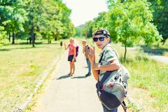Stylish guy in a cap and sunglasses and a backpack with friends goes to study. Children go to school royalty free stock image