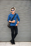 Stylish guy. Cheerful stylish guy with coffee leaning on the wall outdoors Royalty Free Stock Images