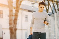 Stylish guy in the city. Stylish man using his phone while walking through the city by himself Stock Photography