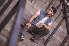 Stylish guy in city. Stylish guy in casual clothes, cap and glasses is sitting on his skateboard on stairs while walking in the city Royalty Free Stock Images