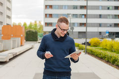 Stylish guy connected on internet with tablet and mobile phone i Royalty Free Stock Image