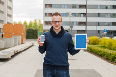 Stylish guy connected on internet with tablet and mobile phone i Royalty Free Stock Photography