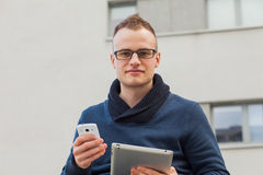 Stylish guy connected on internet with tablet and mobile phone in town. He is happy. Royalty Free Stock Photos