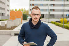 Stylish guy connected on internet with tablet in town. Royalty Free Stock Images