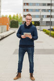 Stylish guy connected on internet with tablet in town. He is hap Royalty Free Stock Photo