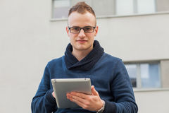 Stylish guy connected on internet with tablet in town. He is hap Stock Photo