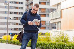 Stylish guy connected on internet with tablet in town. He is hap Stock Images