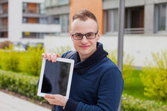 Stylish guy connected on internet with tablet in town. He is hap Royalty Free Stock Photos