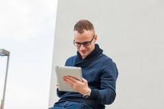 Stylish guy connected on internet with tablet in town. He is happy. Royalty Free Stock Photo