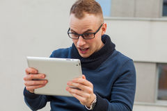 Stylish guy connected on internet with tablet in town. He is sur Royalty Free Stock Images