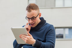 Stylish guy connected on internet with tablet in town. He is sur Stock Image