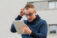 Stylish guy connected on internet with tablet in town. He is sur Royalty Free Stock Photos