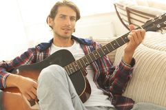 Modern guy with guitar sitting on sofa in living room. Stock Image