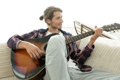 Modern guy with guitar sitting on sofa in living room. Stock Images