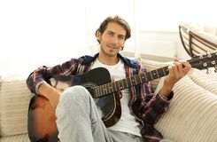 Modern guy with guitar sitting on sofa in living room. Royalty Free Stock Images