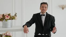 Stylish guy sings in luxury room. Stylish guy singer in costume sings against the backdrop of a bright and luxury room with flowers in a retro style. Young man stock video