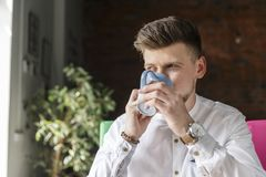 Stylish guy is sitting and drinking coffee from cup. He is looking at window. He is serious and concentrated.  stock images