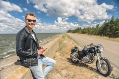 Stylish guy standing next to his motorcycle Stock Photography